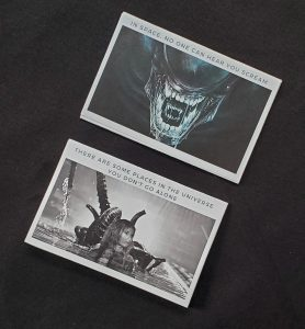 Two zine covers at an angle, showing aliens from the first and second ALIEN movies