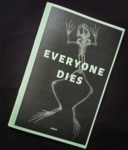 "zine cover is at an angle on a black background, showing a black background with a frog skeleton on the cover with white text that reads ""everyone dies"""