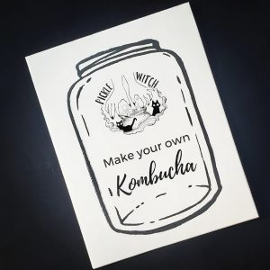 black background with a white zine cover at an angle showing an illustrated jar and lettering