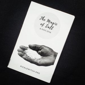 black background with a white zine that has a hand holding a pile of salt