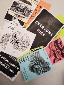 assortment of zines laid out on a white table in a pile