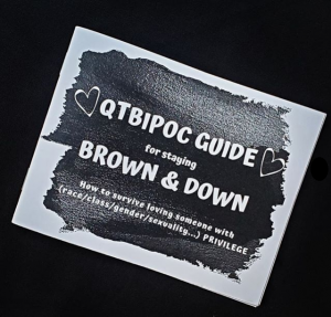 zine cover is at an angle on a black background, with a black shape with white text