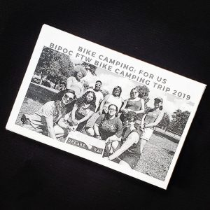 zine cover is at an angle on a black background, with a group photo of people standing and kneeling