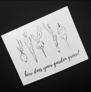 "black background with a white zine which shows black and white line drawings of vegetables, and the text, ""how does your garden grow?"""